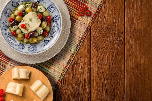 Типичное португальское блюдо с треской под названием bacalhau do porto на оригинальной португальской тарелке, вид сверху.