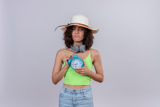 Несчастная молодая женщина с короткими волосами в зеленом топе в шляпе от солнца держит синий будильник на белом фоне
