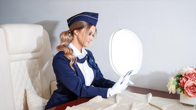 Стюардесса в униформе сидит за столиком возле иллюминатора.