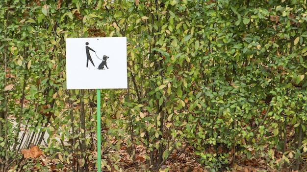 便利なリマインダーは、ドッグパークに入ることです。公園のひもにつないでいる警告サインに犬を置いてください。クリーンな環境とクリーンな社会のための公園内のドッグフードのクリーンなシンボル。