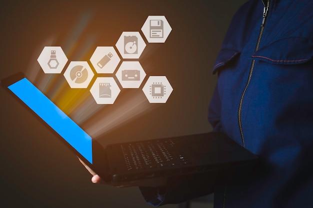 블루 스크린의 컴퓨터 조명이 있는 노트북을 들고 있는 사용자, usb, dvd와 같은 컴퓨터 저장 장치 및 다각형 음영이 있는 관련 아이콘, 데이터 저장 기술 개념