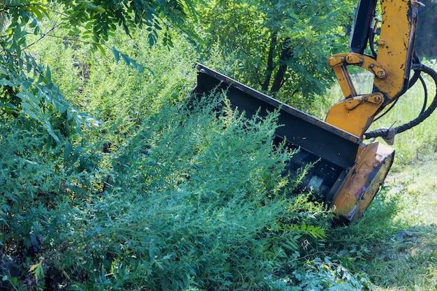 側面に沿って背の高い草を刈るプロのトラクター機械式芝刈り機を使用するユーティリティワーカー