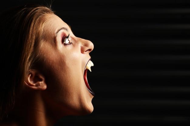 黒の背景で叫んでいる吸血鬼の女性