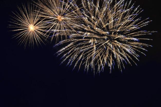 夜空の背景に色とりどりの花火。黄色と金色のフラッシュの花火