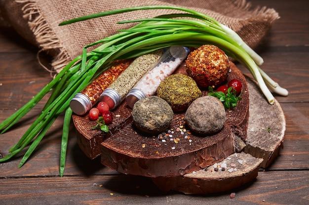 나무 판자에 있는 천에 향신료와 허브를 넣은 다양한 공예 치즈