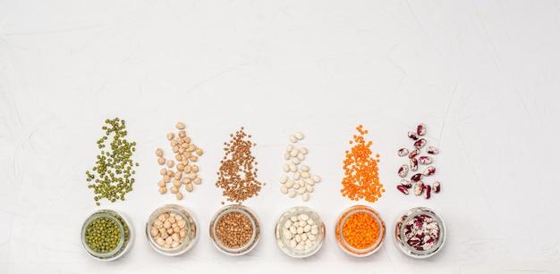 ガラスの瓶に入ったベジタリアン向けのさまざまな乾燥シリアル:レンズ豆、ひよこ豆、豆、そば。コピースペース