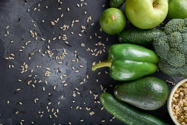 다양한 건강한 날 음식 야채와 과일이 돌 표면에 그룹화됩니다.