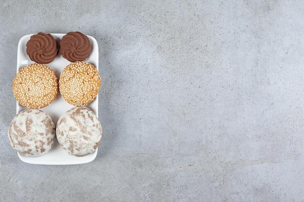 Разнообразное домашнее печенье на тарелке на мраморной поверхности