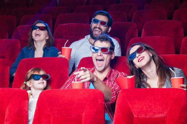 Разнообразие человеческих эмоций от друзей, держащих колу и попкорн в кинотеатре.