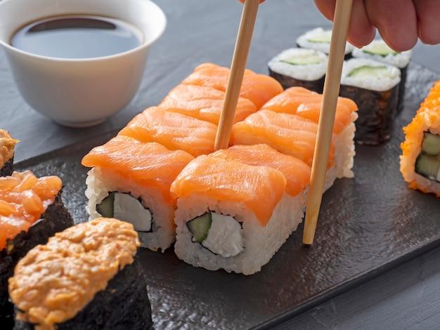 織り目加工の黒いプレートにさまざまな日本のロールと寿司。側面図。 1本のロールを持った竹箸