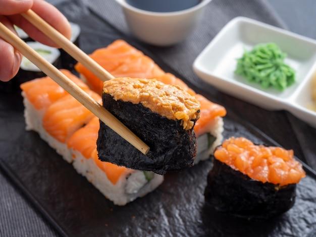 織り目加工の黒いプレートにさまざまな日本のロールと寿司。側面図。竹の棒は1つの軍艦を保持します。閉じる