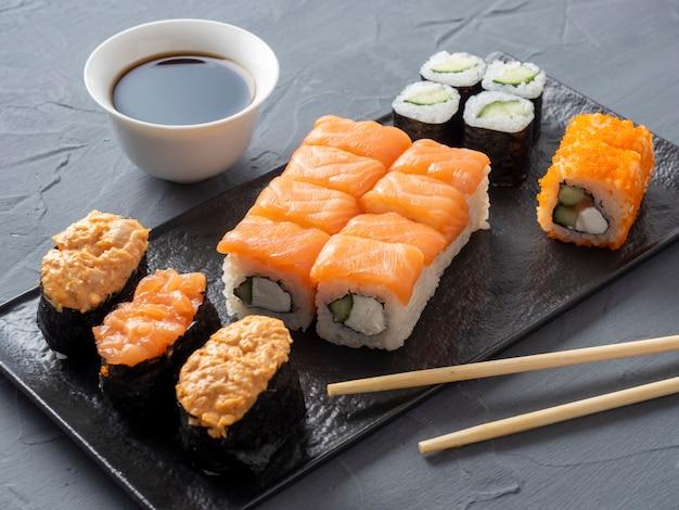 織り目加工のプレートにさまざまな日本のロールと寿司。側面図。近くに生姜とソースの竹の棒。