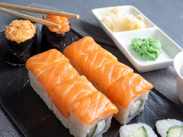 질감 있는 접시에 다양한 일본 롤과 스시. 측면보기. 생강과 소스의 대나무 막대기가 근처에 있습니다.