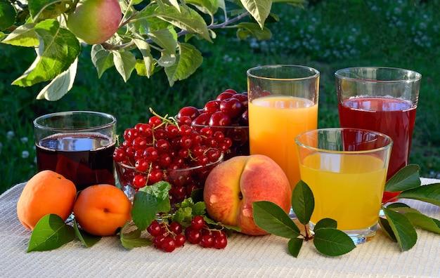 自然な背景にベリーやフルーツを使ったさまざまなジュース