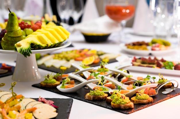 접시에 속이 다른 다양한 미니 스낵. 숟가락과 접시에 진미가있는 연회 테이블에있는 레스토랑의 차가운 전채와 조각