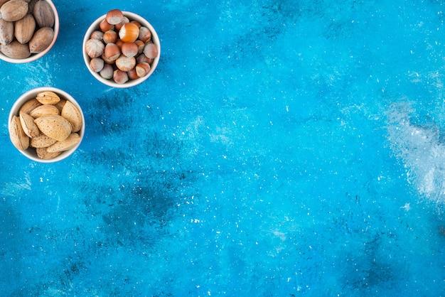 파란색 테이블에 있는 그릇에 있는 다양한 견과류.