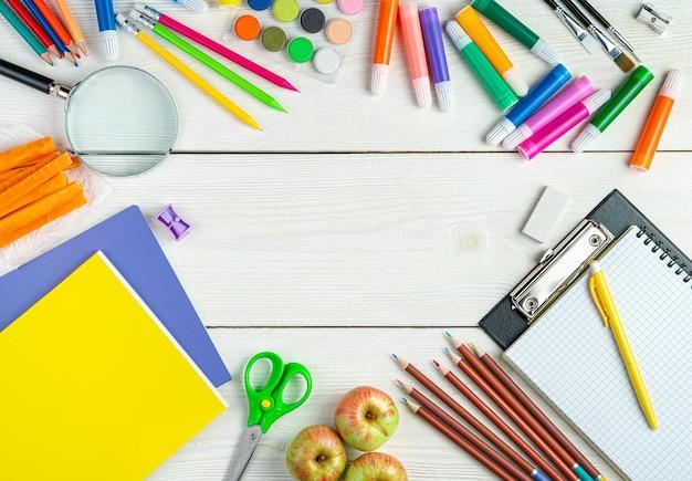 白い木製の背景の上面図のコピースペースにさまざまな事務用品