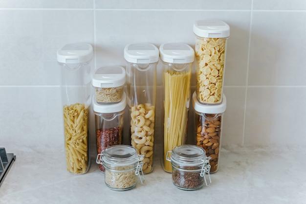 Разнообразные макароны, рис, крупы, орехи в контейнерах-жестяных банках.