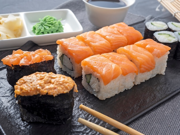 黒いプレートに入れ子になった様々なロールと寿司軍艦。その隣には竹わさびのスティックとソースがあります。側面図。伝統的な日本料理
