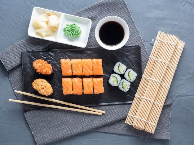 黒いプレートに入れ子になった様々な巻き寿司と寿司軍艦。その隣には竹わさびのスティックとソースがあります。上面図、フラットレイ。伝統的な日本料理