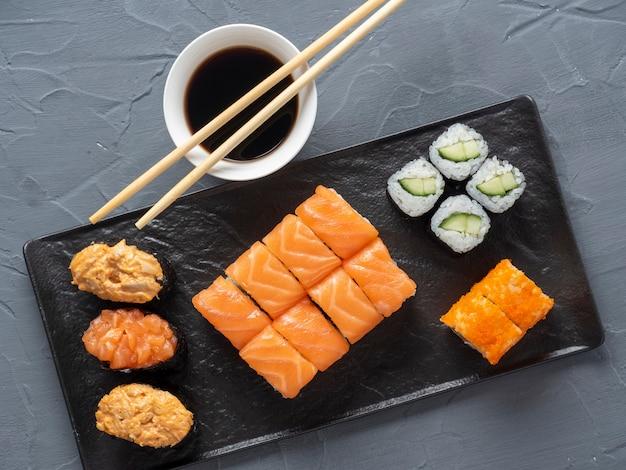 黒いプレートに入れ子になった様々なロールと寿司軍艦。その隣には竹わさびのスティックとソースがあります。上面図、フラットレイ。伝統的な日本料理