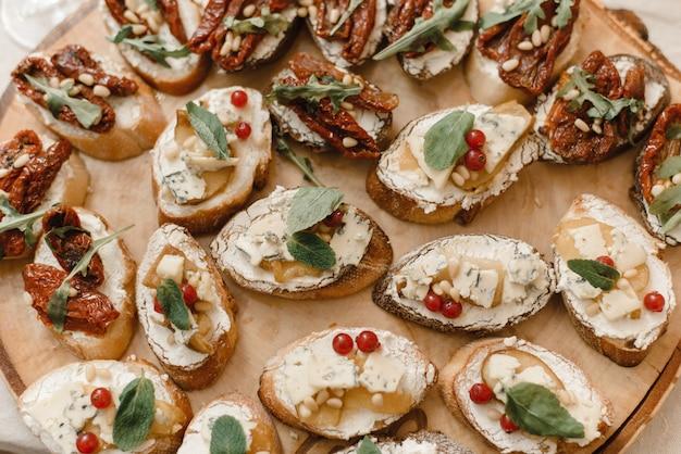 Разнообразные бутерброды и быстрые закуски - тапас на деревянной пиле. испанская специальность