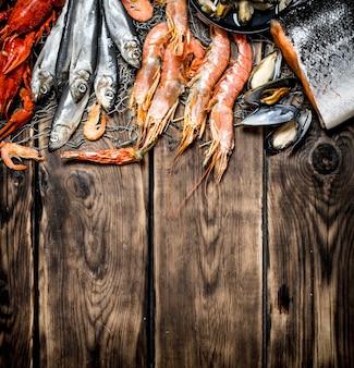 Разнообразие морепродуктов на рыболовной сети на деревянном фоне