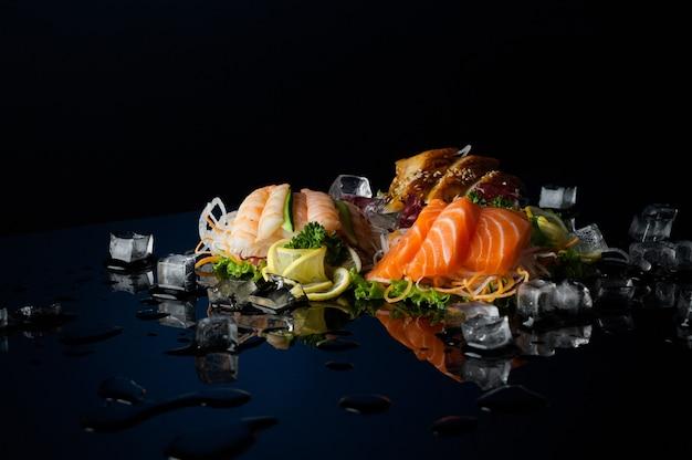 反射のある黒い背景に溶けた氷のかけらが入ったさまざまな寿司