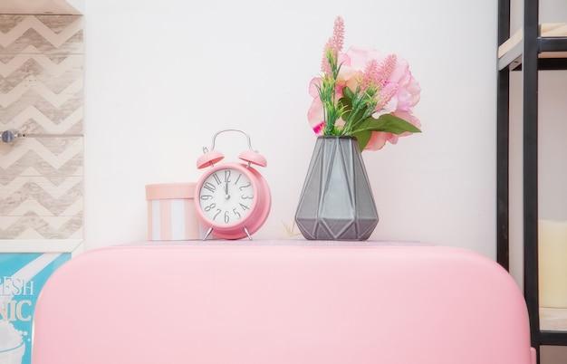 밝은 스칸디나비아 스타일의 주방에서 분홍색 냉장고 지붕에 꽃과 분홍색 알람 시계 꽃병