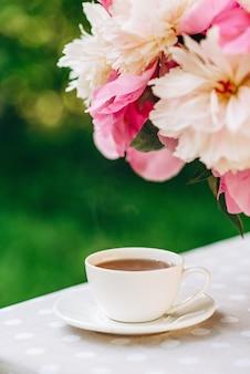 Ваза с цветами пионов возле чашки кофе