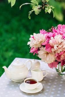 Ваза с цветами пионов возле чашки чая