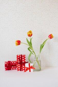 Ваза с букетом красивых тюльпанов и подарочные коробки на столе.