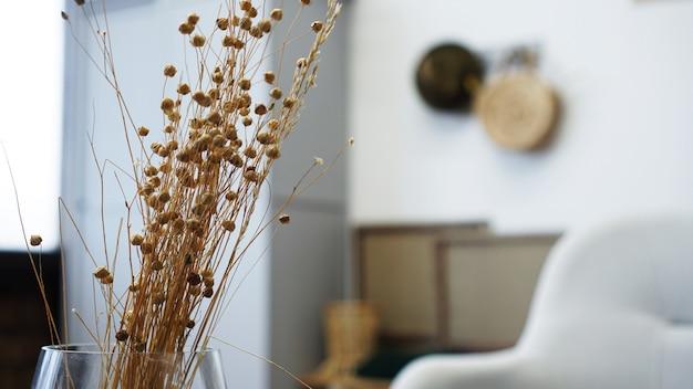 Ваза с сухими цветами на столе. скандинавский классический номер с деревянными и белыми деталями, минималистичный дизайн интерьера. реальное фото. уютный дом.