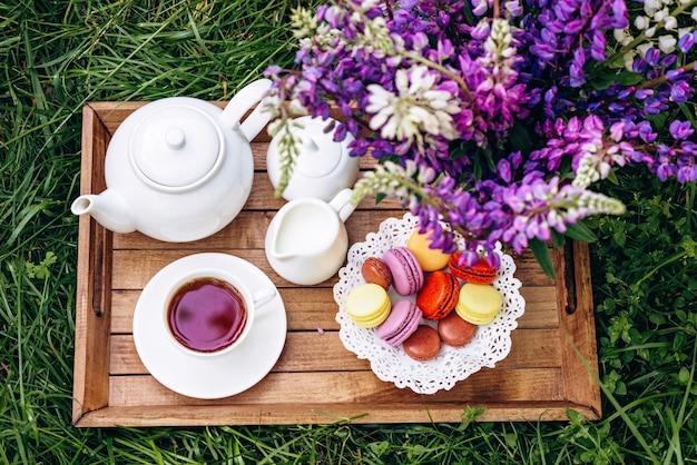 ルピナスの花が入った花瓶、ティーポット、お茶を木製のトレイに