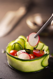 Овощная закуска из свежих овощей, таких как огурцы, помидоры, сыр фета и микрозелень. шеф-повар украшает пинцетом блюдо для гурманов, держа в руках редис. макро, выборочный фокус, покрытие еды