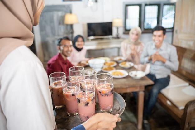 ベールに包まれた女性は、ダイニングルームで一緒に昼食をとりながら、グラスに氷を入れるトレイを運びます