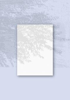 Вертикальный лист белой текстурированной бумаги формата а4 на синей стене