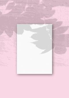 Вертикальный лист белой текстурированной бумаги формата а4 на розовой стене