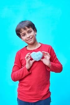 青い壁にぬいぐるみの青いハートを保持している赤いシャツの陽気な黒髪の少年の垂直写真