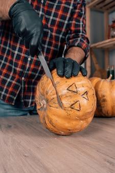 Вертикальный снимок человека в перчатках, режущего тыкву на хэллоуин