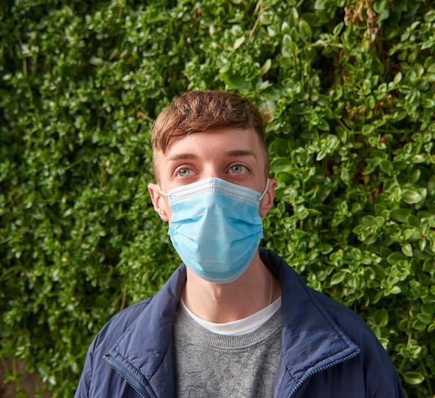 Вертикальный снимок молодого кавказского парня в санитарной маске на открытом воздухе