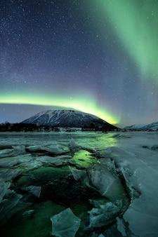 極光の下で雪に覆われた山々の垂直ショット