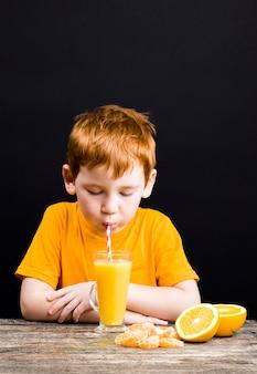 ジュースが作られている柑橘系のフルーツグレープフルーツと非常に美しい赤毛の少年