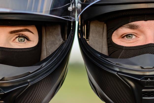互いに寄りかかっているオートバイのヘルメットの男性と女性の非常にクローズアップ