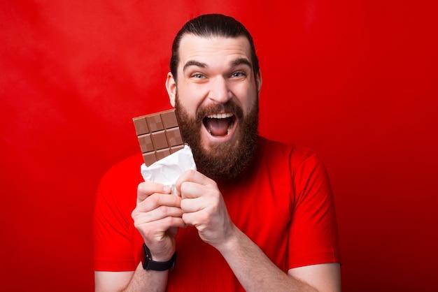 매우 흥분된 남자가 그것을보고 카메라 앞에서 초콜릿을 먹고있다