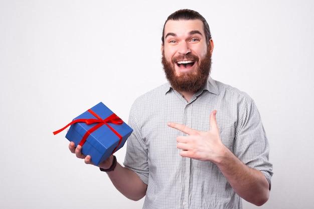 매우 흥분된 남자가 그것을 가리키는 선물을 들고 카메라를 찾고 있습니다
