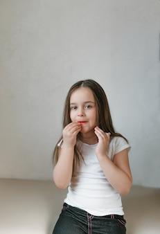 아주 재미있는 어린 소녀가 엄마의 화장으로 화장을하여 입술을 가꾸려고합니다. 행복하고 웃고 감정적 인 아기 얼굴. 여자가되는 법을 배우고, 엄마 립스틱을 시험 해봐
