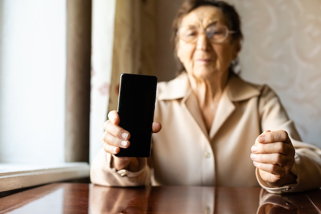 深いしわのある非常に年配の白人の祖母が家に座って、ビデオ通話のために伸ばした腕のフロントカメラで彼女のスマートフォンを使用しています。