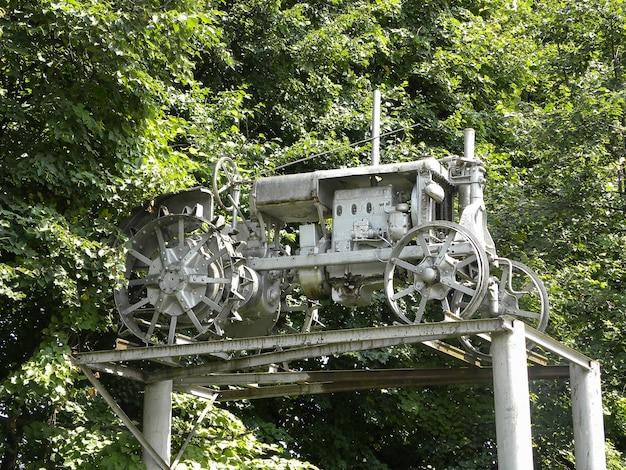 Очень старый трактор, стоит на постаменте, как памятник на фоне деревьев в парке.