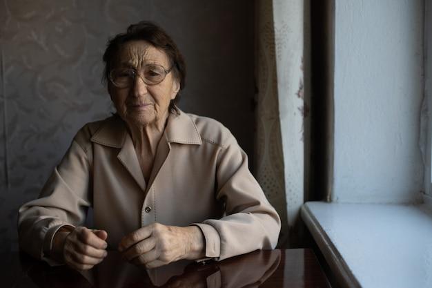 아주 늙은 여자가 안경을 쓰고 카메라를 보고 있다